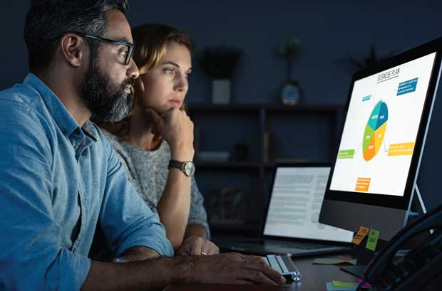 Man and woman looking at analytics screen on computer