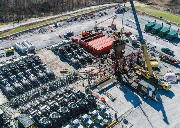 A well site during completion operations, with a frac spread in place on location and an HCU rigged up over the well