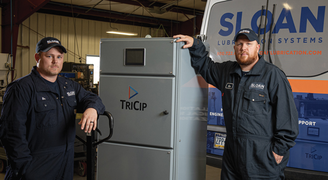 Technicians stand next to the TriCip lubricant delivery system to show that it's about the size of a fridge.