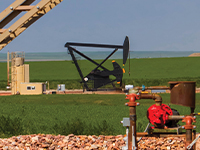 pumpjack with tank equipment in foreground